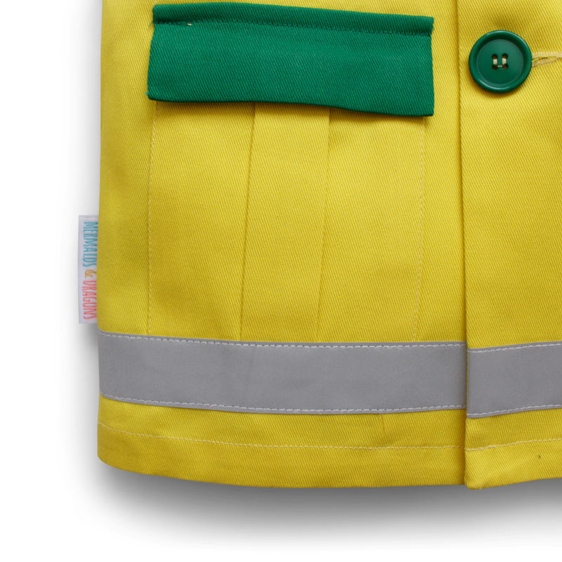 up close of a childrens paramedic uniform showing the box pleat pocket in Yellow and Green cotton twill the hi vis stripe along the hemline, the button closure and the detail of the cotton twill